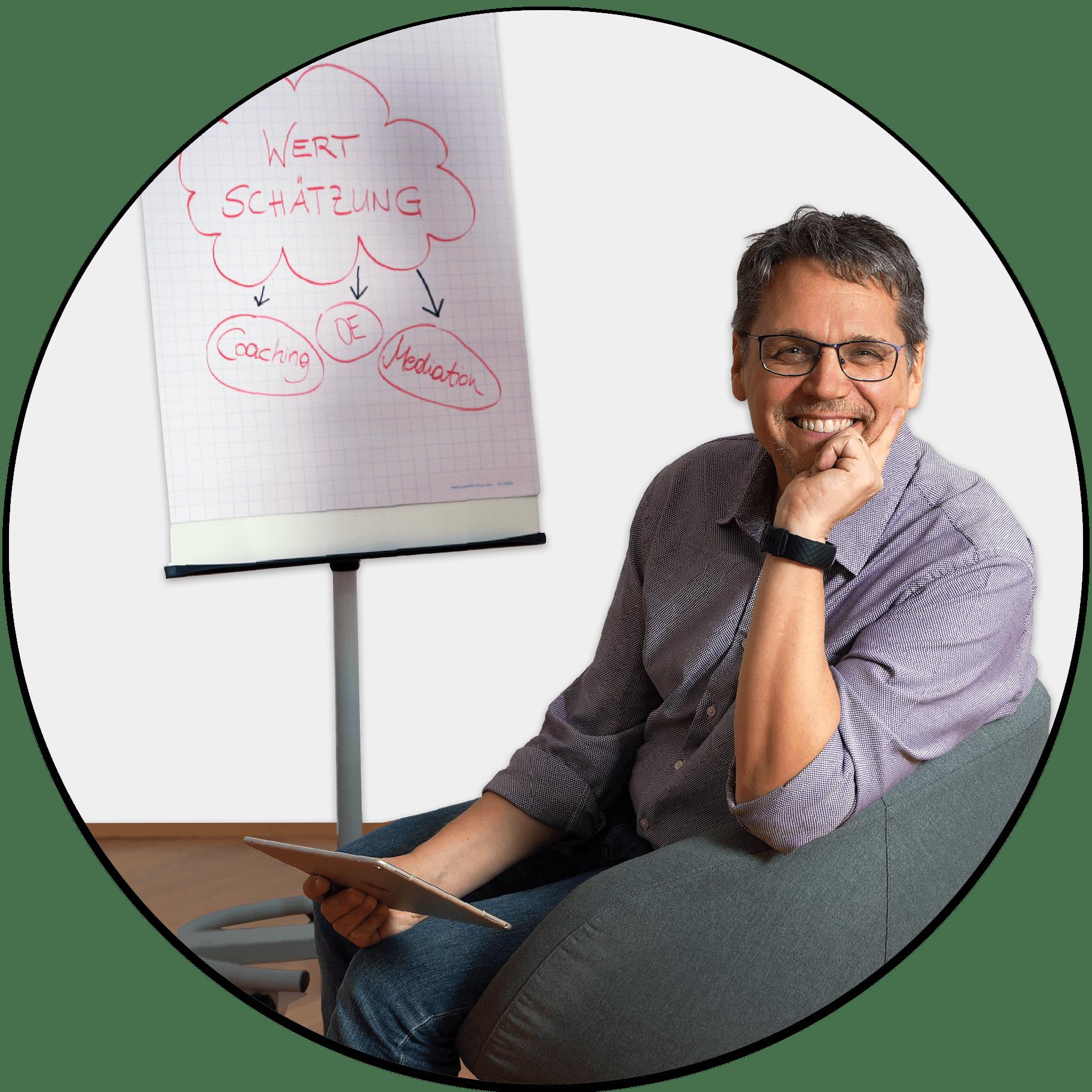 Alfred Schierer sitzend. Im Hintergrund Flipchart mit folgendem Inhalt: Wertschätzung. Coaching, Organisationsberatung, Mediation